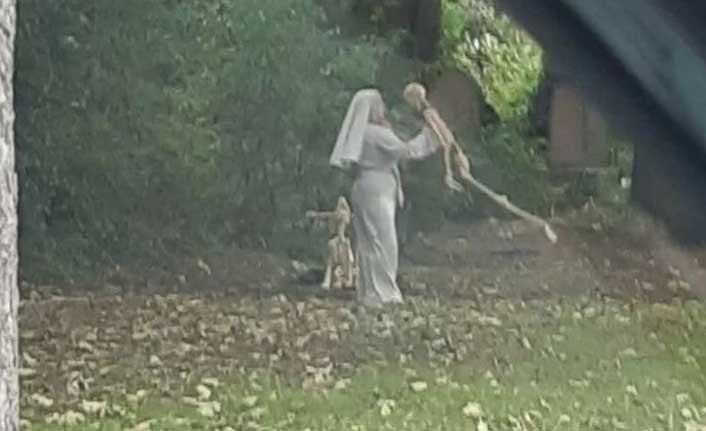 Rahibe elbisesi giymiş bir kadın iskeletle dans etti